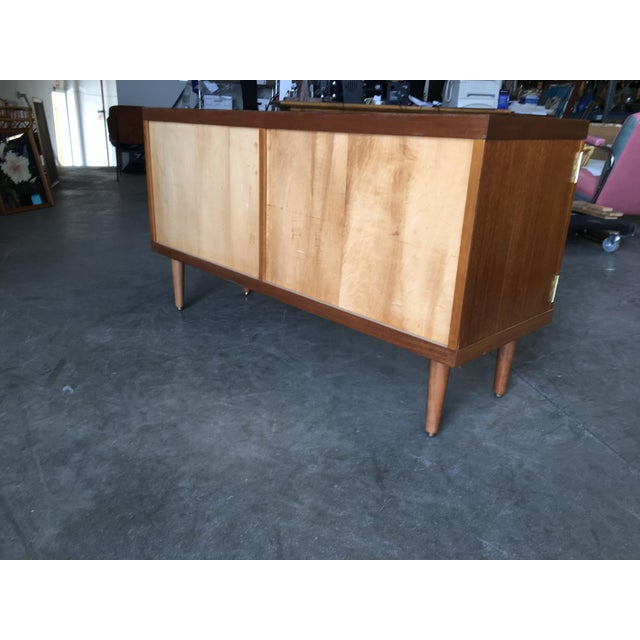 This small Danish style rose stained credenza cabinet with tapered legs, sculpted pig nose pulls and two easy swing doors....