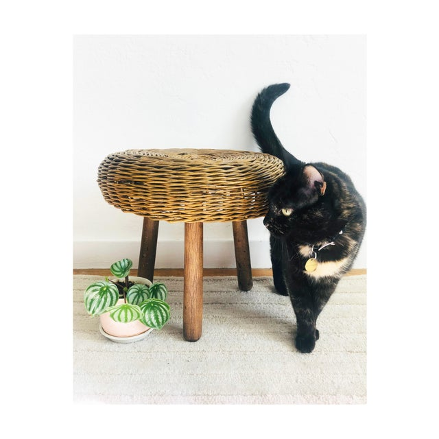 A mid century round wicker stool, design attributed to Tony Paul. Slightly darkened finish to the wicker. Stands on 3...