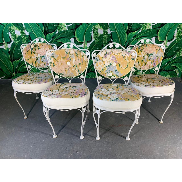 Vintage wrought iron patio set features original floral upholstery and decorative ivy detailing. Includes 4 wrought iron...