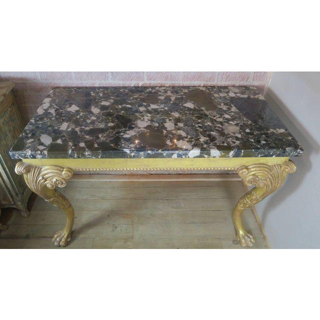 French Rococo style gilt wood console standing on two heavily carved cabriole legs ending in paw feet. Table sits under an...