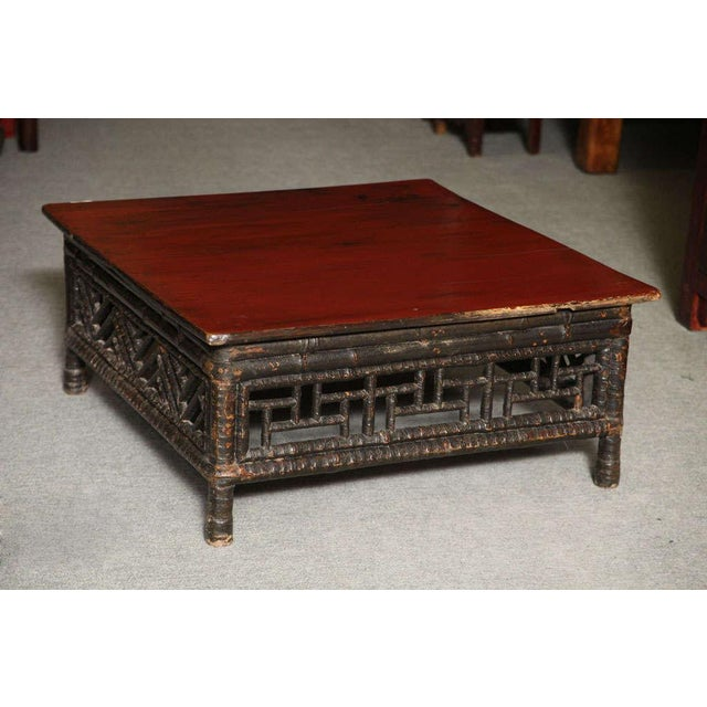 A petite Chinese 19th century coffee table made of bamboo with red lacquered square top. This low coffee table comes from...