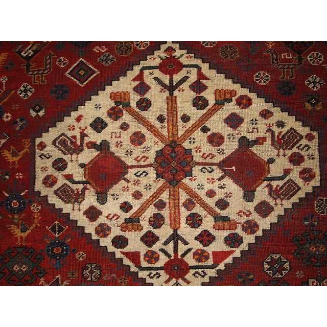 Khamseh Carpet, Southwest Persia, late 19th century, three medium blue and ivory contiguous stepped hexagons on a red...