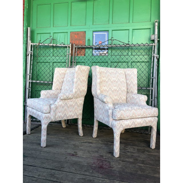 This pair of mid century chairs features original vintage upholstery, wingback design, removable cushions, padded arms.
