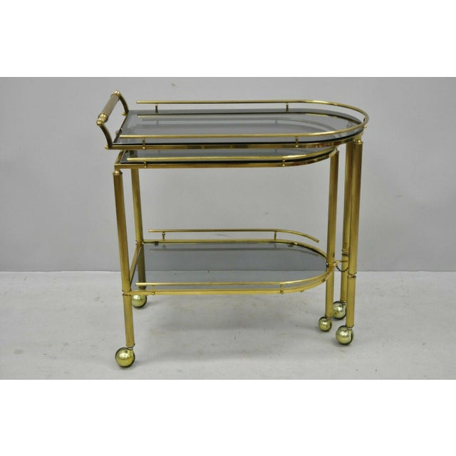 Brass Italian Hollywood Regency swivel extension rolling bar cart server with smoked glass. Item features unique...
