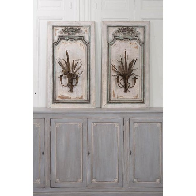 This exquisite pair of Louis XV oak blanc du roi-painted and floral-carved boiserie panels are from a French interior, c....