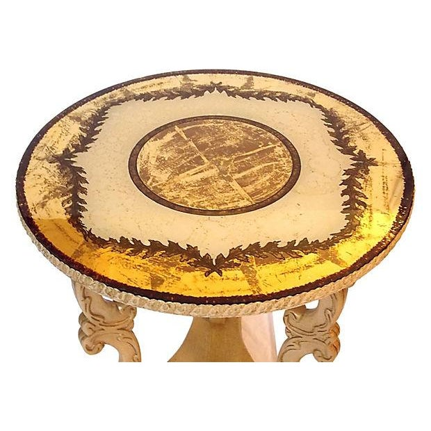 Verre eglomisé round table with three legs, carved in c-scrolls, rest on a triangular platform with bun feet. The verre...