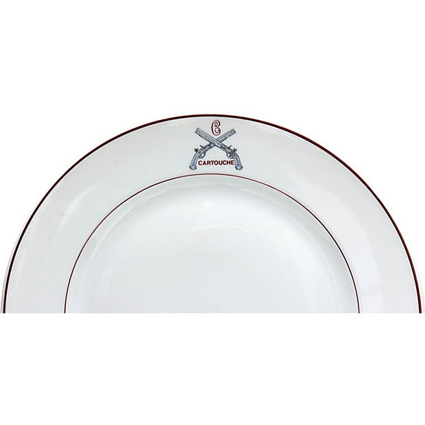 Set of 12 dinner plates with a Paris restaurant logo. Maker's mark on underside. Light wear.
