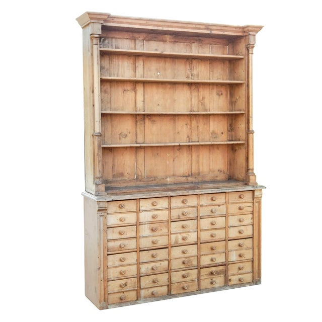 Unusual pine hutch in two pieces -base has 40 small drawers - top has shelves.