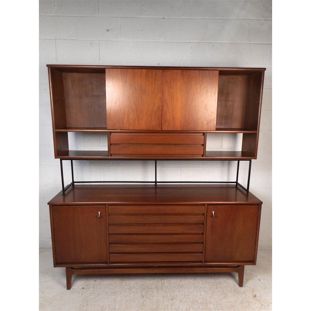 This impressive midcentury piece features a sturady finished walnut construction including a finished back, a credenza...