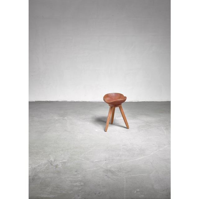 A Swedish low tripod wooden stool with a sculptural seating, carved out from a solid piece of wood. Outside curving is the...