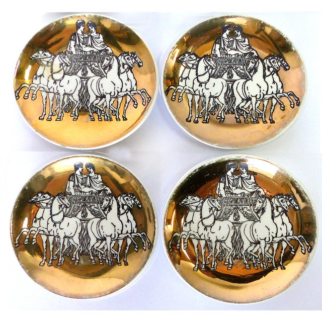 A rich gold porcelain set of four lovely Piero Fornasetti Roman Chariot coasters. The coasters feature a Roman male and...
