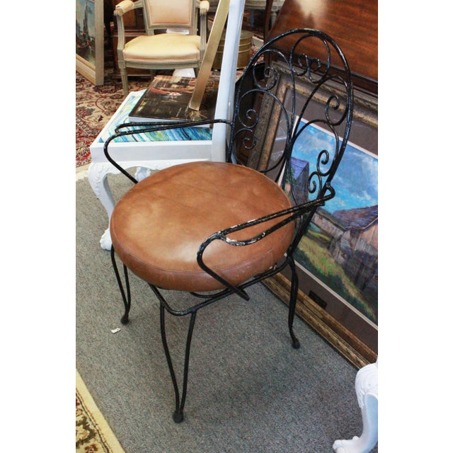 Indoor dining table set of a round marble table with four wrought iron chairs painted black with brown leather cushions....