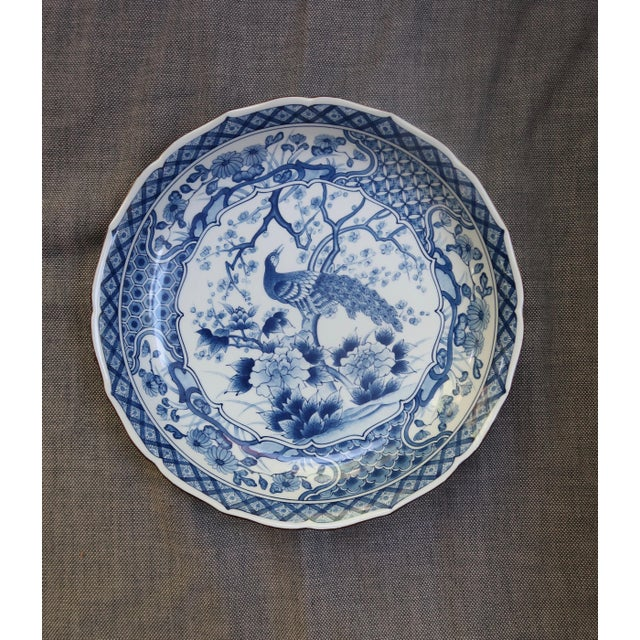 Large blue and white Chinese charger / plate / bowl with intricate peacock design and scalloped edge. Signed on bottom.