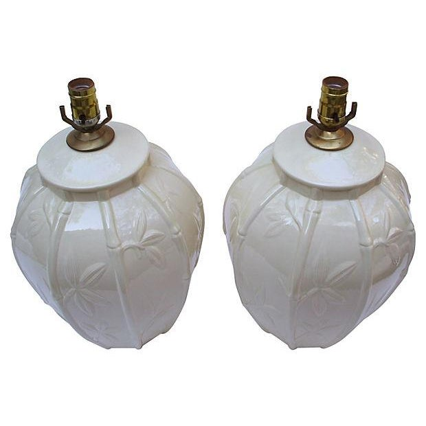 A stunning pair of creamy white ceramic lamps, designed with raised bamboo details. The original wiring is in working...