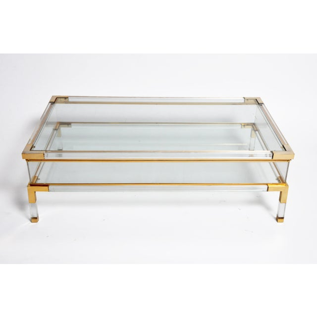This sleek vitrine table has a glass top that slides opens to reveal a storage space below. Walled with Lucite, the clear...