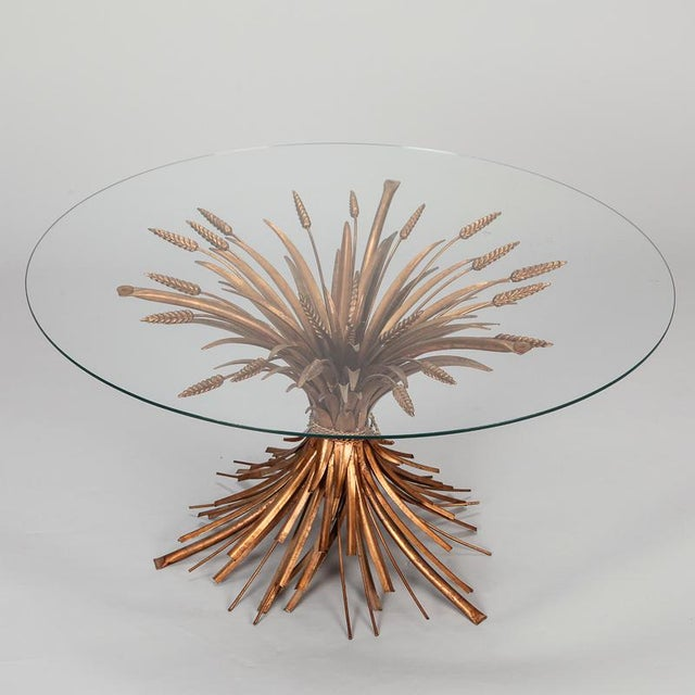 Circa 1940s cocktail or side table has a gilded metal base in the form of gathered wheat sheaves with a round glass table...