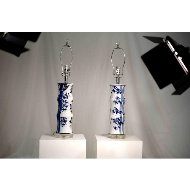 This Oriental blue and white ceramic table lamps with a pattern of bamboo hand painted on the white column body. White...