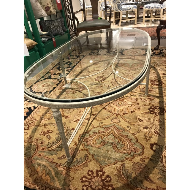 "Minton Spidell iron and glass coffee table. Distressed painting in off white. 1/2"" Glass with 1/2"" bevel."
