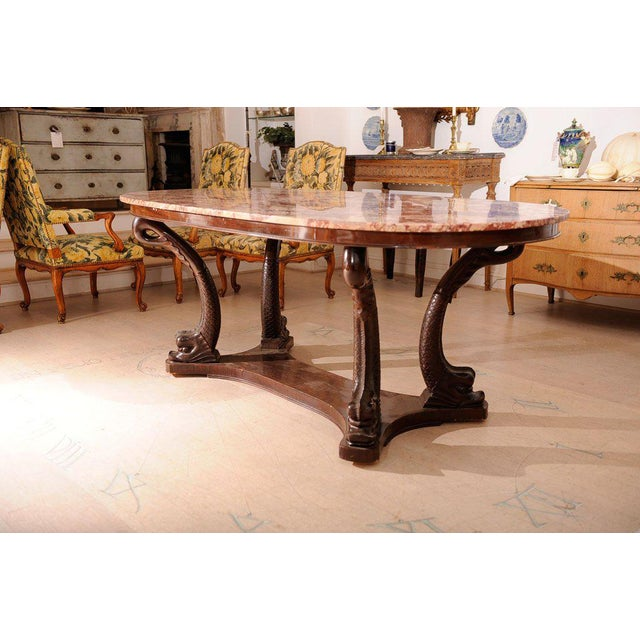 An Italian oval dining table with rose marble top with carved mahogany dolphin motif decoration base.