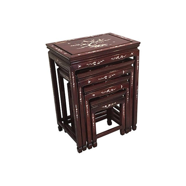 Set of four Chinese rosewood nesting tables with inlaid mother-of-pearl. Done in different scenes which include peacocks,...
