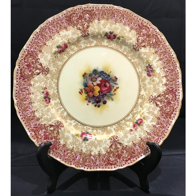 Set of 10 Vintage burgundy and gold Royal Worcester dinner plates. These plates feature a detailed floral motif in the...