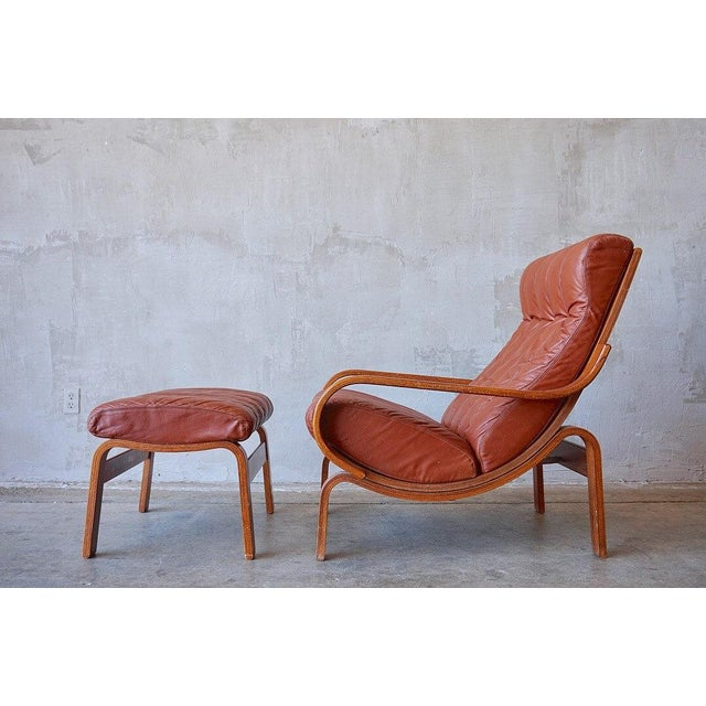 Stunning pair of oversized shapely wood and leather lounge chairs by Westnofa, c. 1970s. With the high back rests, deep...