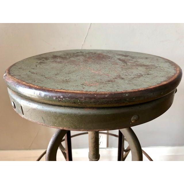 Vintage steel Uhl Toledo stool with wood seat. Worn gray/green paint.