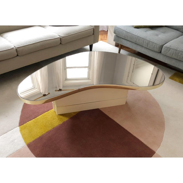Unique mirrored top kidney-shaped coffee table. Mirror top has a bronze tint, and a brass trim. Off-white lacquered...