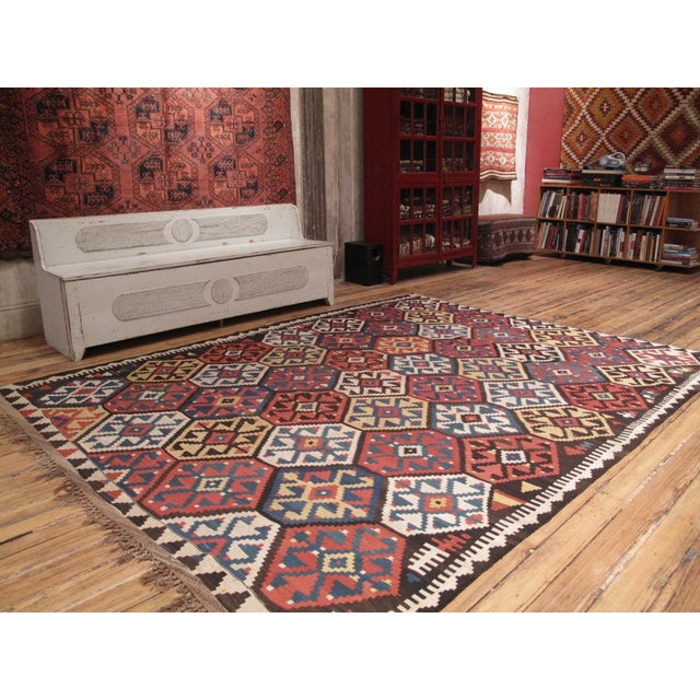 A fantastic antique Kilim, in a rare large, squarish size, featuring a well-known design and brilliant colors in natural...