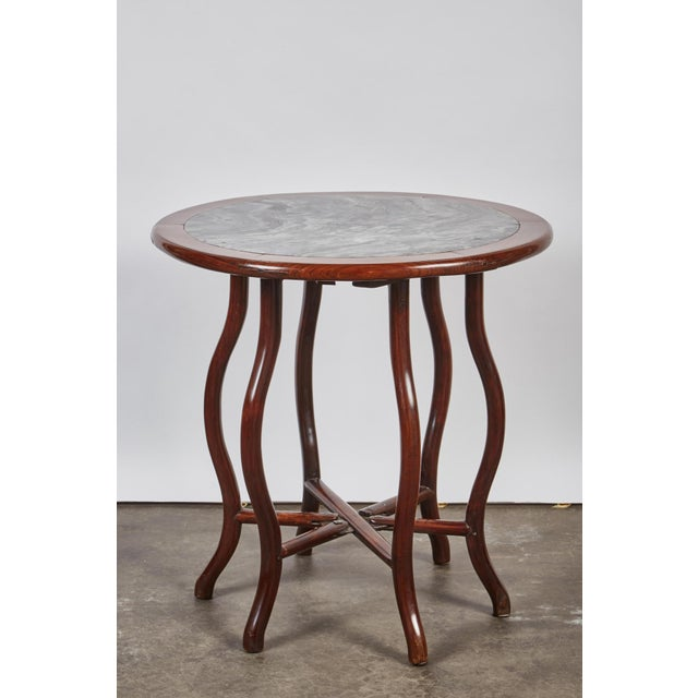 A two piece folding table, from the Qing Dynasty, that has a rosewood base with a white and gray marble detachable table...