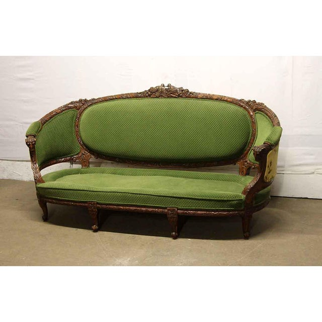 Green upholstered Victorian sofa with a highly carved figural dark wood tone frame. The top has two kissing birds and the...