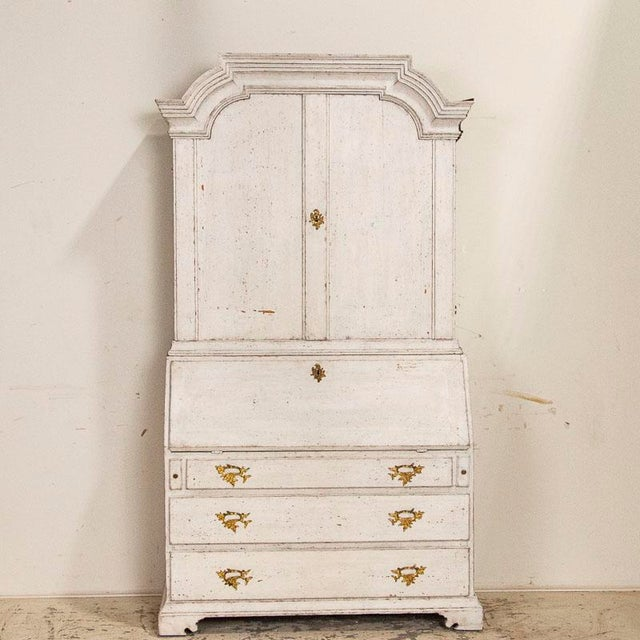 Stately and elegant, this tall white gustavian pine secretary shows off with the distinctive shape of the top bonnet or...