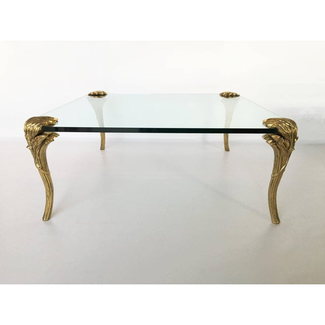 A great P. E. Guerin NY design glass top and bronze coffee table. The thick glass top supported by four chased gilt bronze...