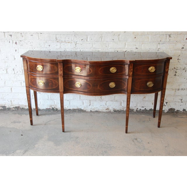 Offering an exceptional inlaid mahogany Hepplewhite style sideboard from the Heirlooms Collection by Drexel Heritage. The...