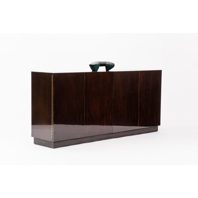 Dark brown finished walnut with leather plinth base. Accordion doors. 12 pull-out drawers on left and right side, four...