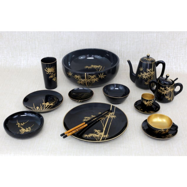 A complete, vintage set of fine Japanese black lacquerware. Each piece has a different gold floral design and gold trim....