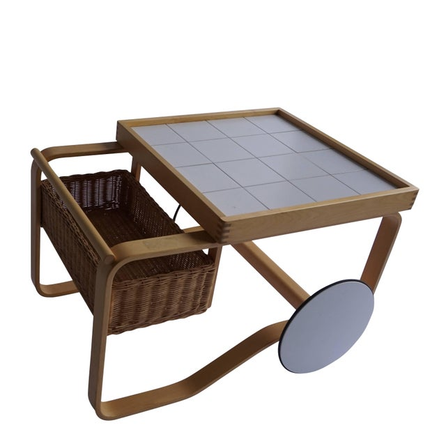 Alvar Aalto tea cart, the top is made of white tiles, which are inset in a wooden frame. The basket serves for additional...