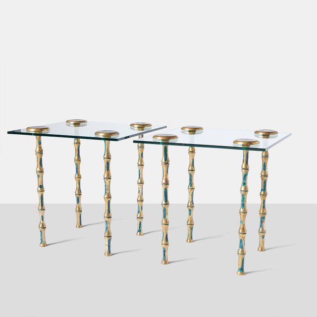 A pair of side or coffee tables with glass top and decorated solid brass legs. The four legs attach thru the glass top...
