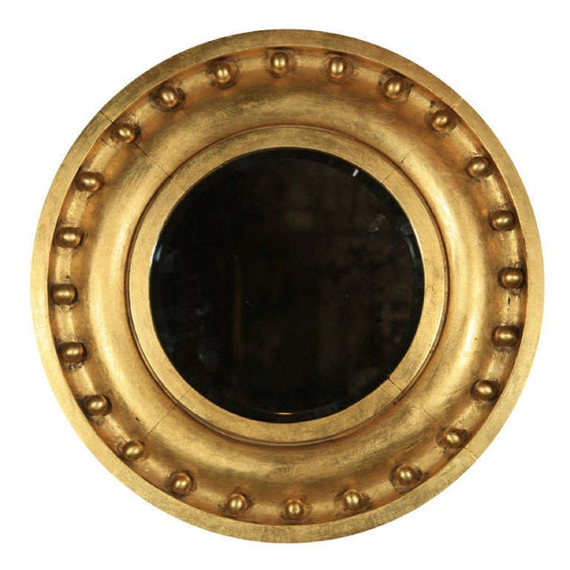 Offered is an antique, gilded circular mirror. The circular molded frame decorated with beads.
