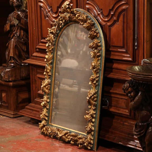 Add old world beauty into your home with this antique heavily carved mirror from Spain, circa 1850. The mirror has a...
