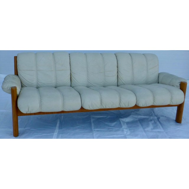 Three-seat sofa with sculptural solid teak frame and vintage cream colored leather upholstery. Produced by J.E. Ekornes,...