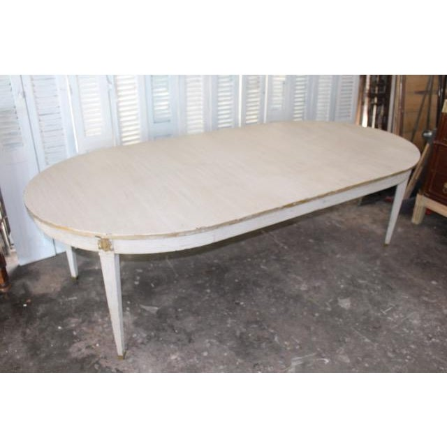 Beautiful 18th century French provincial dining table. Newly refinished in an off white patina with gold leaf trim....