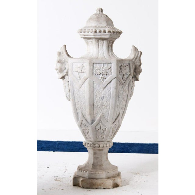 A classic large pair of marble finials or urns in carved marble. Featuring grotesque masks, grapes and beading along with...