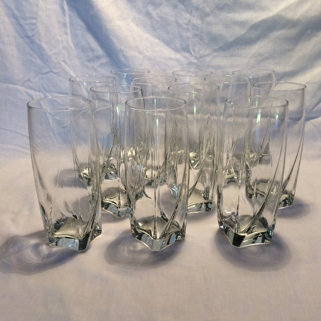Simple clean set Of 12 tall crystal water glasses. The base is thick and square and there is a subtle twist in the...
