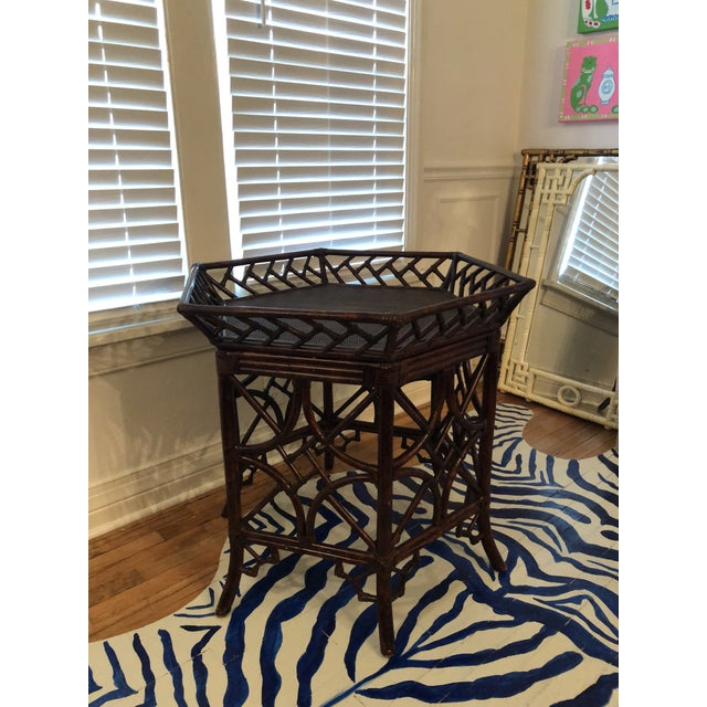 Rattan tray table with tons of fretwork. The top tray is removable. The condition is consistent with age. Some loss of...