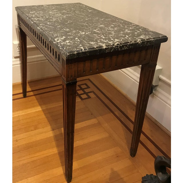French fruitwood console table with black cut and beveled marble top. Beaded edge skirt. 18th century.