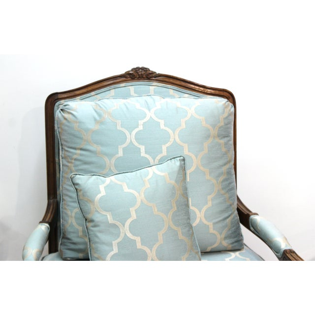 French Louis XV provincial style pair of bergere armchairs with pale blue upholstery and pillows. The pair is in great...