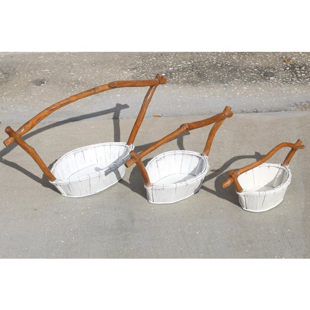 A set of three nesting white wood baskets with wood handles. Good vintage condition; minor wear consistent with age and...