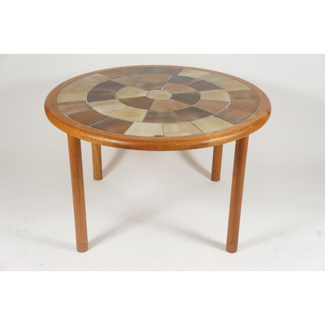 A great sized sturdy teak with ceramic tile top dowel legged dining/dinette in teak. The table is designed by Tue Poulsen...