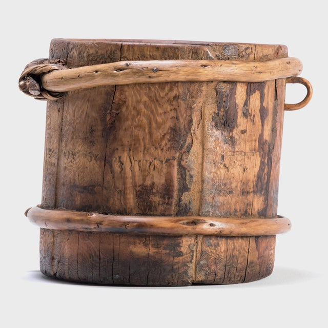 This container was made over a century ago in Mongolia to store grains. It was made to last: the sturdy pine wood slats...